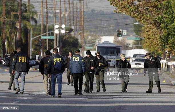 Law enforcement personnel continue to investigate on San Bernardino Avenue, where two suspects in the mass shooting at the Inland Regional Center...