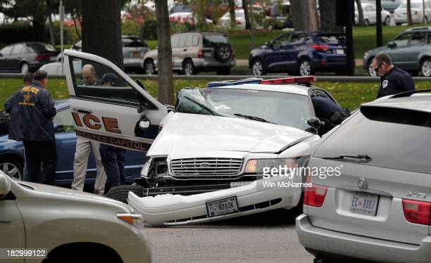 Law enforcement personnel gather around a police vehicle that was involved in an incident with another vehicle on Constitution Avenue outside the US...