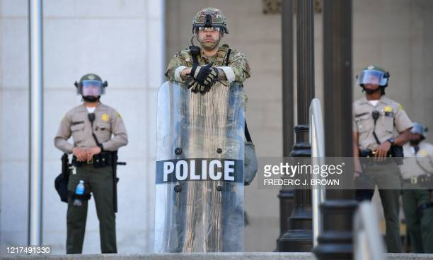 Law enforcement personnel in riot gear face protesters in Los Angeles California on June 3 2020 where people gathered to protest the death of George...