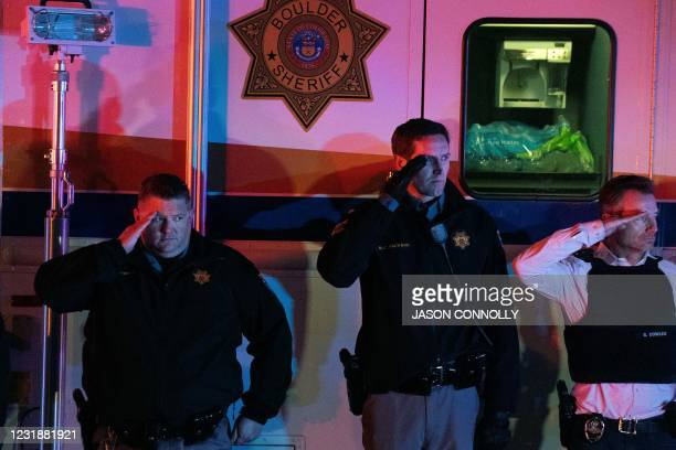 Law enforcement personnel salutes as the motorcade carrying fallen Boulder Police officer Eric Talley exits the King Soopers grocery store in...