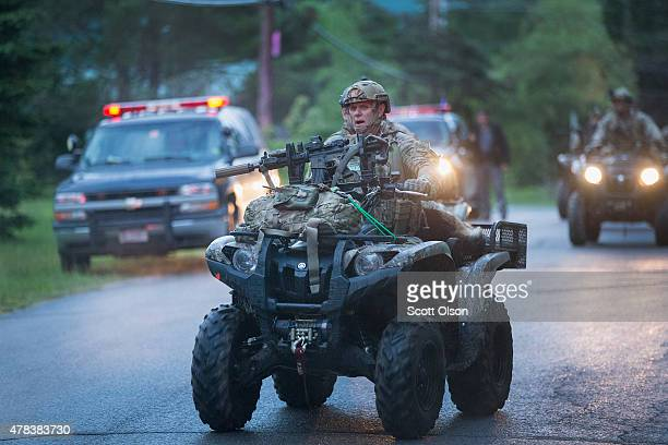 Law enforcement personnel search a wooded area after they received a tip that convicted murderers Richard Matt and David Sweat were in the area on...