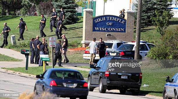 Law enforcement personnel walk outside the Sikh Temple of Wisconsin where at least one gunman fired upon people at a service on August 2012 Oak Creek...