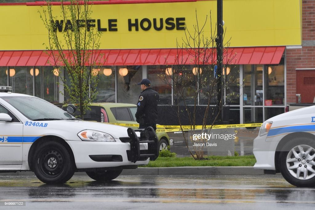 Law enforcement stand outside a Waffle House where four people were killed and two were wounded after a gunman opened fire with an assault weapon on April 22, 2018 in Nashville, Tennessee. Travis Reinking, 29, of Morton, IL, is person of interest in the shooting and is suspected to have left the scene naked.