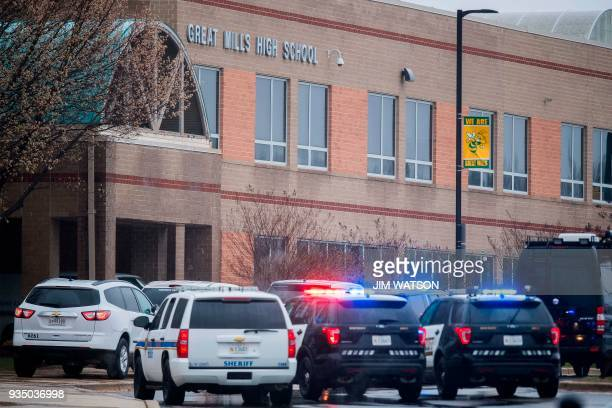 Law enforcement vehicles are parked in front of the Great Mills High School in Great Mills Maryland after a shooting at the school on March 20 2018 A...