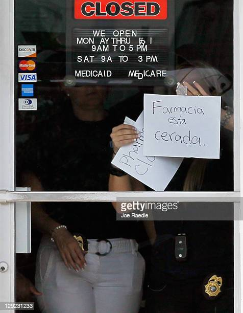 Law enforment agents place a closed sign in the door of the Cabana Pharmacy after it was raided by the City of Miami Police Department's Crime...