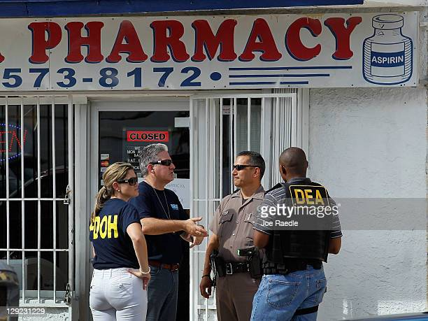Law enforment agents stand outside of the Cabana Pharmacy after it was raided by the City of Miami Police Department's Crime Suppression Unit and...