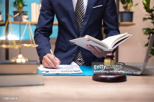 law, lawyer attorney and justice concept, male lawyer or notary working on a documents and report of the important case in the law firm,bangkok,thailand. date 02/27/2019 - legislation stock pictures, royalty-free photos & images