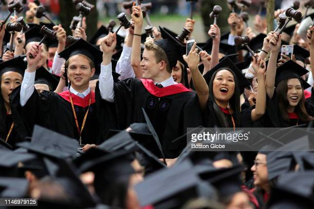 Law school graduates hold gavels aloft during the 2019 Harvard University commencement on Harvard Yard in Cambridge MA on May 30 2019