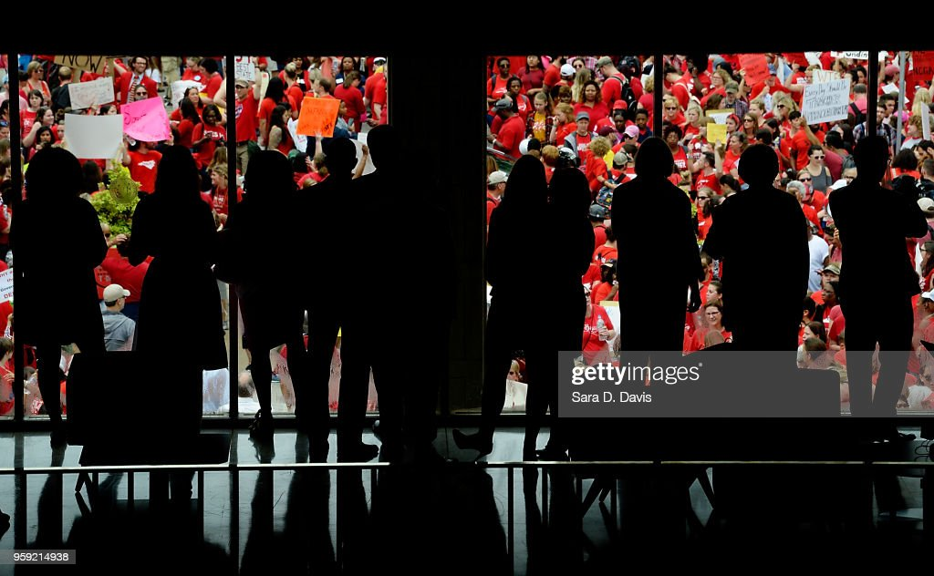 Lawmakers and legislative employees watch the crowd grow outside of the North Carolina Legislative Building on May 16, 2018 in Raleigh, North Carolina. Several North Carolina counties closed schools to allow teachers to march on the opening day of the General Assembly.