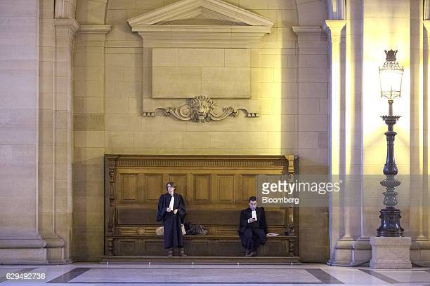 Lawmakers sit on a wooden bench inside the hallway of the Palais de Justice in Paris France on Tuesday Dec 13 2016 Christine Lagarde now the...