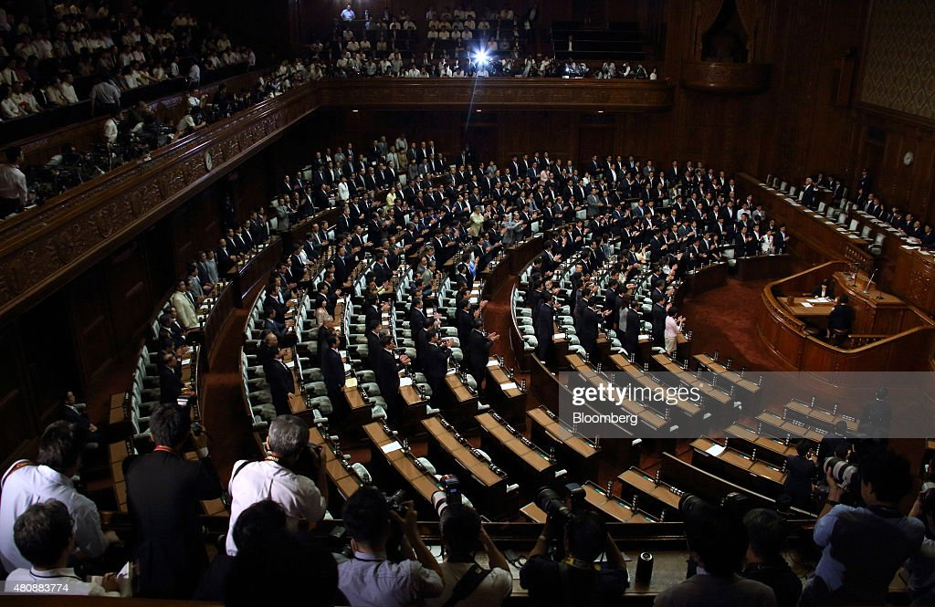 Lawmakers stand as the security bills passes during a plenary session at the lower house of the parliament in Tokyo, Japan, on Thursday, July 16, 2015. Abe's security bills passed parliament's lower house Thursday after a night of noisy protests, as his push to expand the role of the military risks further eroding his public support. Photographer: Tomohiro Ohsumi/Bloomberg via Getty Images