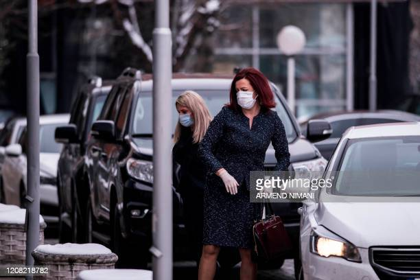 Lawmakers wearing protective masks and gloves arrive for an extraordinary session at the Kosovo Parliament in Pristina on March 25, 2020 - Kosovo's...