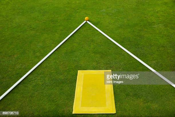 A lawn bowls green edge, a yellow players mat to stand on and two white lengths of wood, guidelines with a yellow jack ball at the apex.