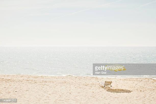 Lawn chair and umbrella on beach