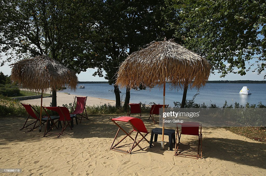 Lawn chairs and a beach await visitors on the shore of artificial Senftenberger See lake on August 26, 2013 in Grosskoschen, Germany. Senftenberger See was once an open-pit lignite coal mine flooded after it shuttered in the late 1960s, and today it is popular among tourists, wind surfers and fishermen. In a development project initiated by state government, other nearby former open-pit mines that once evoked a lunar landscape are being turned into lakes in a long-term rejuvenation effort that is also intended to make the area a viable tourist destination. Mineral residue in the mines, however, is proving a difficult stumbling block that is making many of the new lakes too acidic to sustain marine life in the short term.