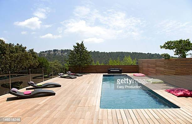 Lawn chairs and pool on modern deck