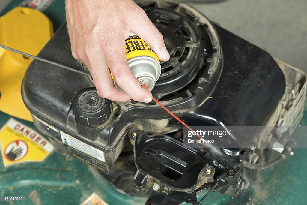 Lawnmower Carburetor Cleaning With Spray Stock Photo - Getty