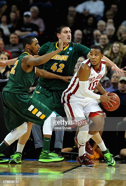 Lawrence Alexander and Marshall Bjorklund of the North Dakota State Bison defend Jordan Woodard of the Oklahoma Sooners during the second round of...