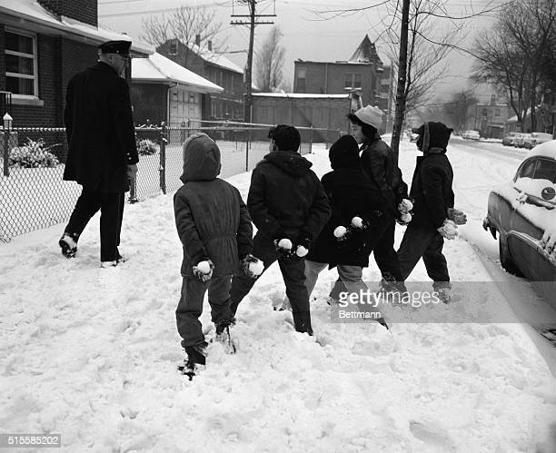 Lawrence Berry Ray Doro Paul Kauslarich Bob Toloriello and Morris Underwood hide snowballs behind their backs as police officer Vincent Blake walks...