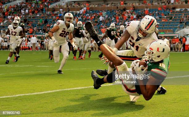 Lawrence Cager of the Miami Hurricanes makes a touchdown catch over Juan Thornhill of the Virginia Cavaliers during a game at Hard Rock Stadium on...