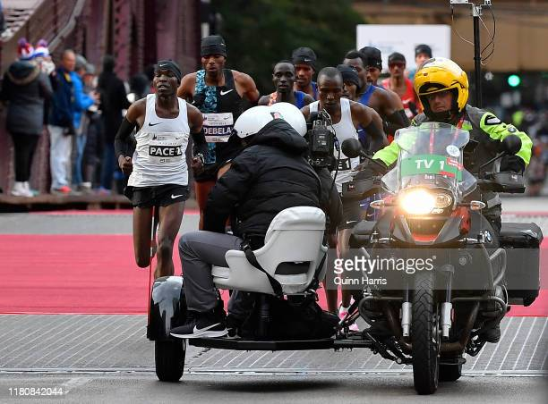 Lawrence Cherono of Kenya and Dejene Debela of Ethiopia run behind the pacers during the 2019 Bank of America Chicago Marathon on October 13, 2019 in...