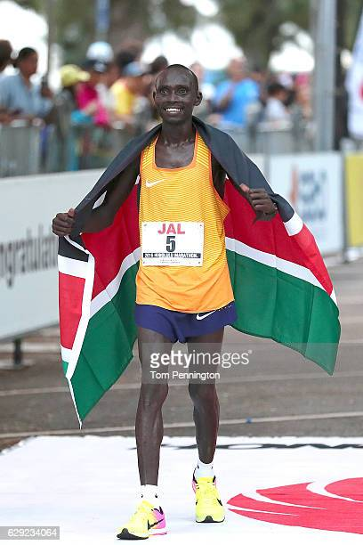 Lawrence Cherono of Kenya celebrates with flag after crossing the finish line during the Honolulu Marathon 2016 on December 11, 2016 in Honolulu,...