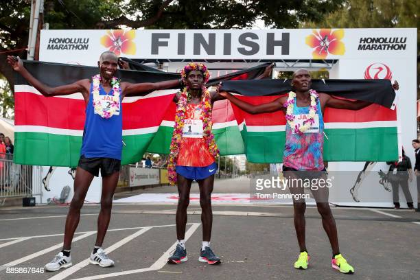 Lawrence Cherono of Kenya in second place, Dennis Kimetto of Kenya in first place and Titus Ekiru in third place pose with flags after winning the...