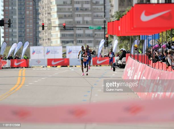 Lawrence Cherono of Kenya races to the finish line in front of Dejene Debela of Ethiopia during the 2019 Bank of America Chicago Marathon on October...