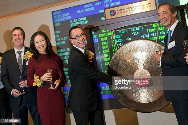 Lawrence Ho cochairman and chief executive officer of Melco Crown Entertainment Ltd second from right strikes a gong as wife Sharen Ho second from...