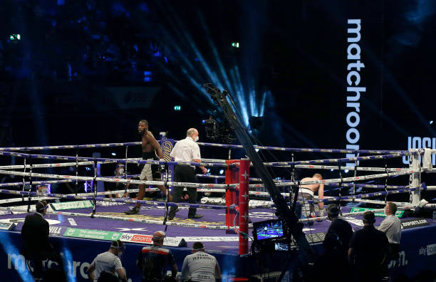 Lawrence Okolie walks to the corner as referee Phil Edwards checks on Nikodem Jezewski after he is knocked down during the WBO International...