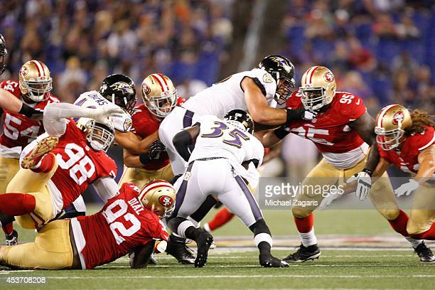 Lawrence Okoye and Quinton Dial of the San Francisco 49ers tackle Cierre Wood of the Baltimore Ravens during the game at MT Bank Stadium on August 7...