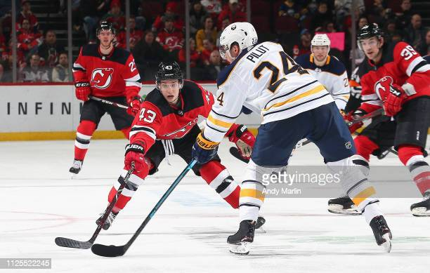 Lawrence Pilut of the Buffalo Sabres controls the puck while being defended by Brett Seney of the New Jersey Devils during the game at Prudential...