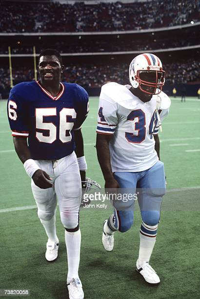 Lawrence Taylor and Earl Campbell walk off the field together after their game at the Meadowlands in 1982