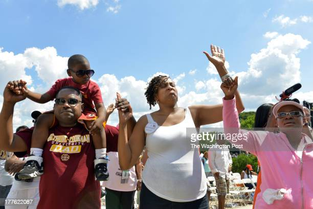 Lawrence Taylor of DC, L, holding his son Trayvon Taylor Ingrid Nurse of Concord, NC, and Saymendy Lloyd hold hands in prayer at the 50th anniversary...
