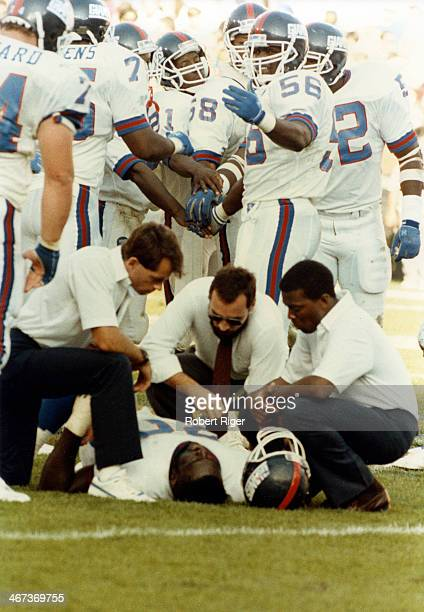 Lawrence Taylor of the New York Giants gathers the team around as his teammate lies injured on the ground during their game against the Los Angeles...