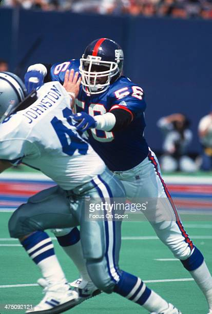 Lawrence Taylor of the New York Giants hits Daryl Johnston of the Dallas Cowboys during an NFL football game September 30 1990 at The Meadowlands in...