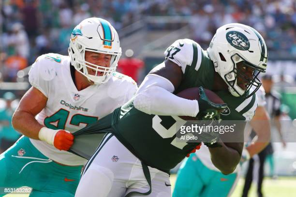 Lawrence Thomas of the New York Jets is wrapped up by Kiko Alonso of the Miami Dolphins during the second half of an NFL game at MetLife Stadium on...
