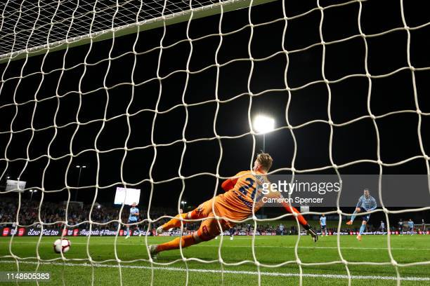 Lawrence Thomas of the Victory attempts to stop a penalty goal by Adam Le Fondre of Sydney FC during the A-League Semi Final match between Sydney FC...