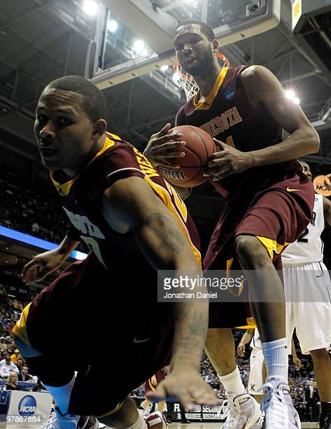 Lawrence Westbrook of the Minnesota Golden Gophers falls out of bounds alongside teammate Damian Johnson in the second half against the Xavier...