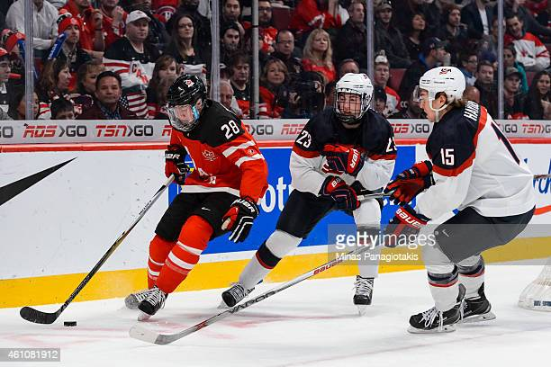 Lawson Crouse of Team Canada carries the puck with Zach Werenski of Team United States and teammate John Hayden following close behind in a...