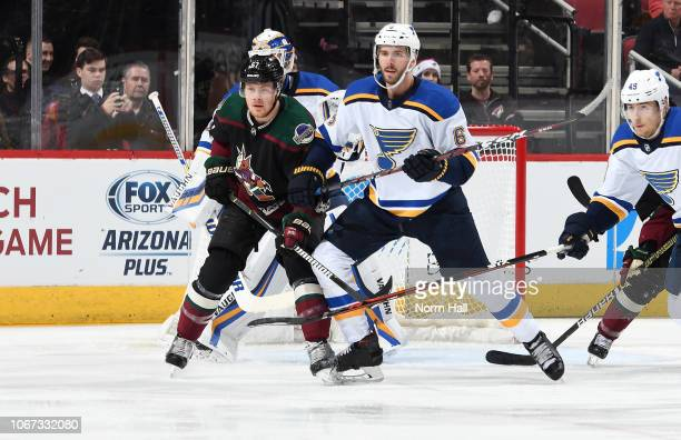 Lawson Crouse of the Arizona Coyotes and Joel Edmundson of the St Louis Blues battle for position in front of goalie Chad Johnson of the Blues during...