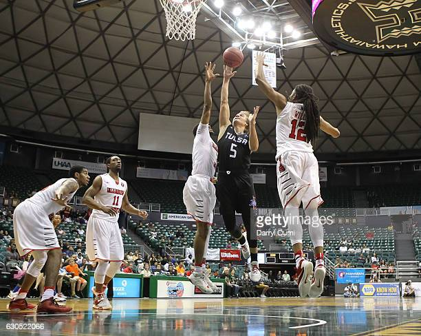 Lawson Korita of the Tulsa Golden Hurricane puts up a shot between two Illinois defenders during the second half of the Diamond Head Classic third...