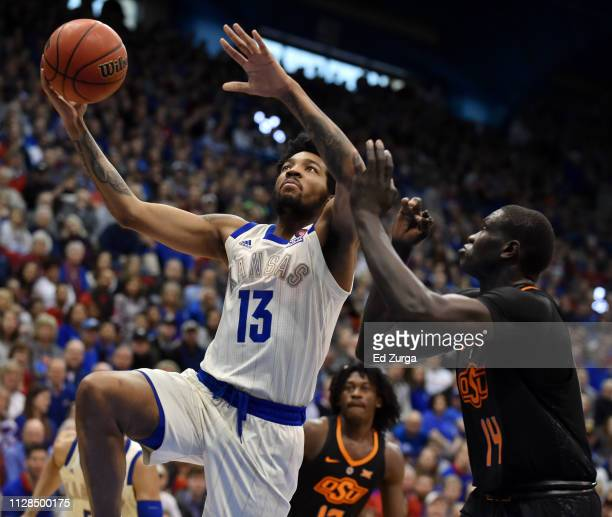 J Lawson of the Kansas Jayhawks lays the ball up against Yor Anei of the Oklahoma State Cowboys in the first half at Allen Fieldhouse on February 09...