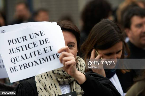 A lawyer brandishes a placard reading 'For a Justice of quality and proximity' The French Bar Association all lawyers' unions all magistrates' unions...