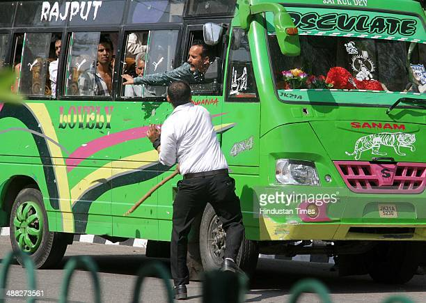 A lawyer breaks the side mirror of a local transport during Jammu Bandh call given by Bar Association and various other organizations on May 5 2014...