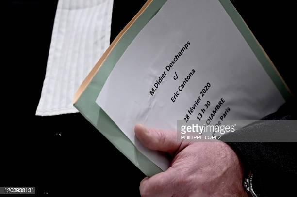 A lawyer carries a file of the case opposing former French football player Eric Cantona and French football team head coach Didier Deschamps at Paris...