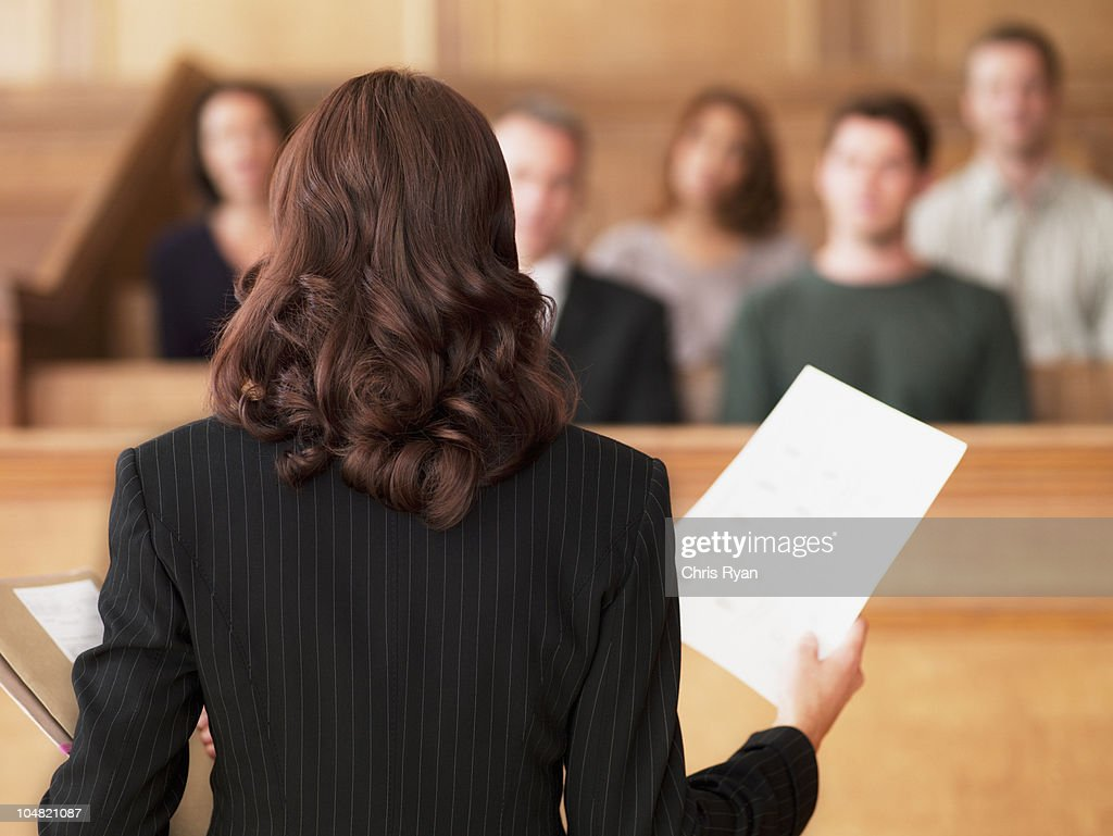 Lawyer holding document and speaking to jury in courtroom : Stock Photo