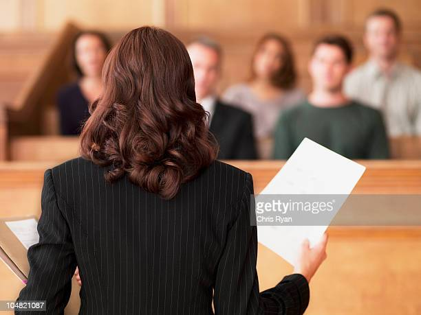 lawyer holding document and speaking to jury in courtroom - courtroom stock pictures, royalty-free photos & images