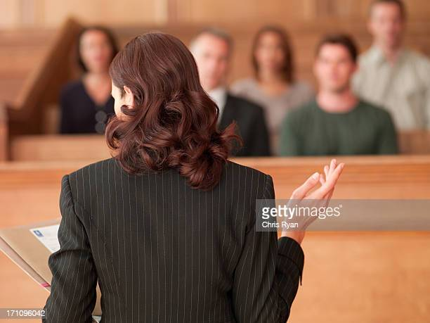 lawyer holding document and speaking to jury in courtroom - juror law stock pictures, royalty-free photos & images