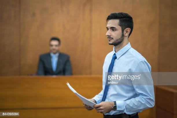 lawyer holding documents in the courtroom - courtroom stock pictures, royalty-free photos & images